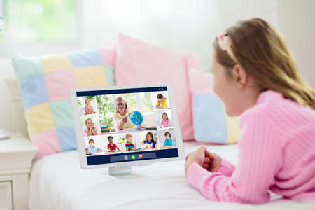 Online remote learning. School kids with computer having video conference chat with teacher and class group. Child studying from home. Homeschooling during quarantine and coronavirus outbreak. Banco de Imagens