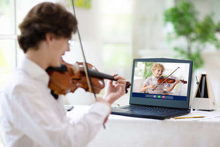 Violin lesson online. Teacher and child play violin via computer. Remote learning from home. Arts for kid. Kids with musical instrument. Video chat conference. Online music tuition. Homeschooling.