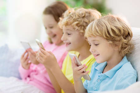 Kids with mobile phone. Child with tablet computer watching movie or playing game. Group of little children with digital device and gadget. Screen time and education for young kid. Friends play.