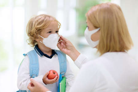 Family with kids in face mask going to school or kindergarten. Mother and child wear facemask during coronavirus and flu outbreak. Virus and illness protection, hand sanitizer in public crowded place. Stock Photo