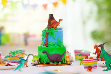 Kids birthday party. Dinosaur theme layer cake. Children event. Decoration for dinosaurs themed celebration.