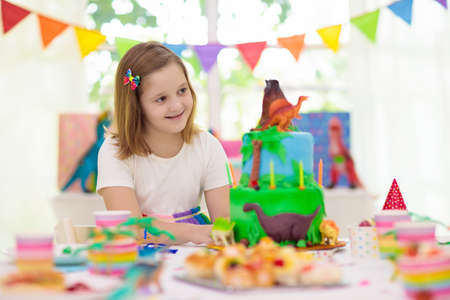 Kids birthday party. Dinosaur theme cake. Little girl blowing candles and opening gifts. Children event. Decoration for dinosaurs themed celebration. Banque d'images