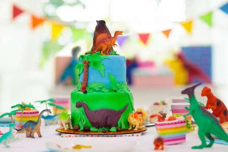 Kids birthday party. Dinosaur theme layer cake. Children event. Decoration for dinosaurs themed celebration. Stock Photo