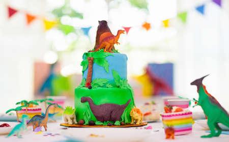 Kids birthday party. Dinosaur theme layer cake. Children event. Decoration for dinosaurs themed celebration.