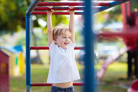 Child playing on outdoor playground in rain. Kids play on school or kindergarten yard. Active kid on colorful monkey bars. Healthy summer activity for children. Little boy climbing.