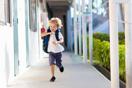 Child going to school. Boy running in school yard. Little student excited to be back to preschool or kindergarten. Beginning of class after vacation. Kids run to parents or friends after lesson.