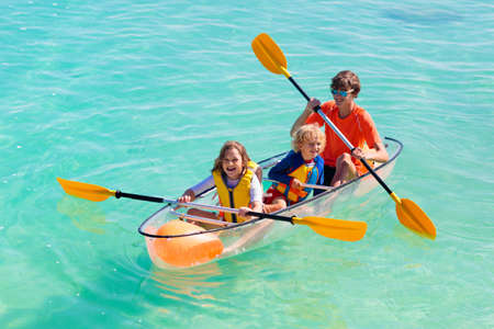 Kids kayaking in ocean. Children in kayak in tropical sea. Active vacation with young kid. Parents, little boy and girl in canoe on beautiful beach. Holiday activity with child. Family water fun.