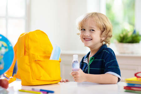 School child with backpack, face mask and sanitizer. Student safety after coronavirus pandemic. Virus and disease prevention for kids. Back to school and kindergarten after covid-19 outbreak. Stockfoto