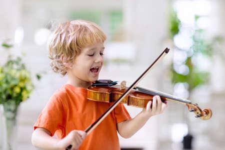 Enfant jouant du violon. Apprentissage à distance depuis la maison. Arts pour les enfants. Petit garçon avec instrument de musique. Leçon de conférence par chat vidéo. Cours de musique en ligne. Les enfants créatifs jouent la chanson. Enseignement classique