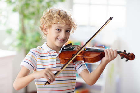 Child playing violin. Remote learning from home. Arts for kids. Little boy with musical instrument. Video chat conference lesson. Online music tuition. Creative children play song. Classical education 写真素材