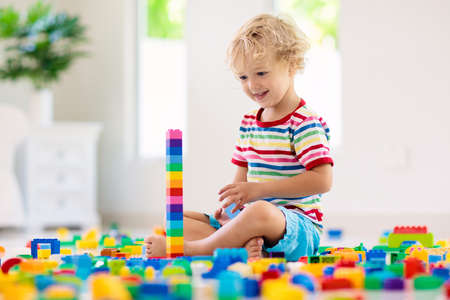 Child playing with colorful toy blocks. Little boy building tower at home or day care. Educational toys for young children. Construction block for baby or toddler kid. Mess in kindergarten play room. Stockfoto