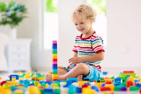 Kind, das mit bunten Spielzeugklötzen spielt. Turm des kleinen Jungen zu Hause oder in der Kindertagesstätte. Lernspielzeug für kleine Kinder. Baublock für Baby oder Kleinkind. Chaos im Kindergartenspielzimmer. Standard-Bild