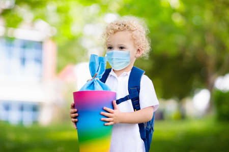 Child wearing face mask with traditional German candy cone on the first school day. Back to school in virus outbreak. Student with backpack and books during covid-19 pandemic. Coronavirus in Germany.