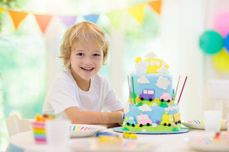 Kids birthday party. Boy cake with car and airplane. Child blowing out candles on colorful cake. Party decorations, rainbow flag banners, balloons. Vehicle theme celebration. Kid celebrating birthday