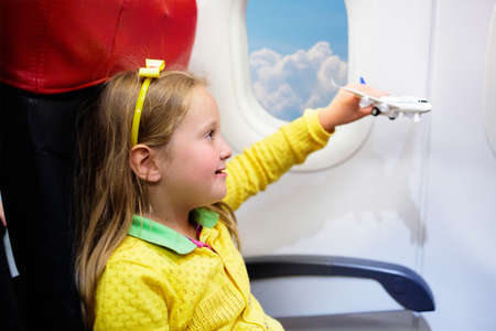 Child in airplane. Kid in air plane sitting in window seat. Flight entertainment for kids. Traveling with young children. Kids fly and travel. Family summer vacation. Little girl with toy in airplane Foto de archivo