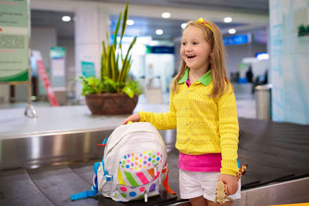 Kids at airport luggage belt. Children travel by airplane. Traveling and flying with child. Family at arrival hall collecting bags and suitcase. Little girl with backpack waiting for bag after flight.