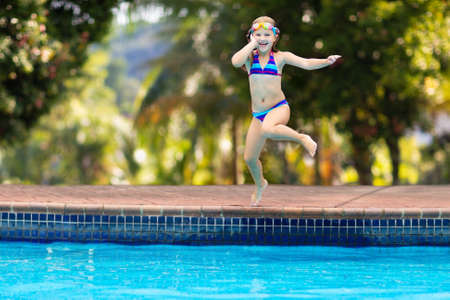 Child jumping into water in swimming pool. Kids swim and play on family summer vacation in tropical resort. Little girl diving. Travel with young children. Healthy outdoor activity. Beach fun.