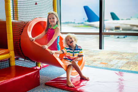 Kids at airport playground. Children look at airplane. Traveling and flying with child. Family at departure gate. Vacation and travel with young kid. Boy and girl before flight in terminal.