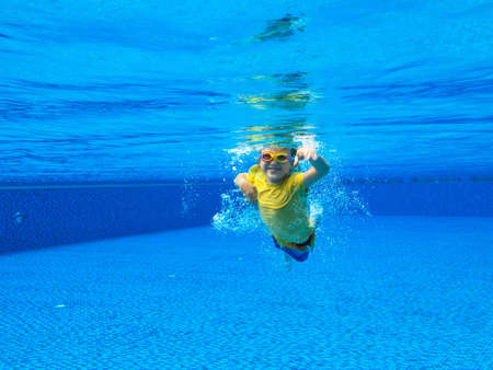 Child underwater in swimming pool. Kids swim. Little boy diving under water in tropical resort. Healthy outdoor sport for kid. Family summer vacation. Water and beach fun. Swim wear and sun protection