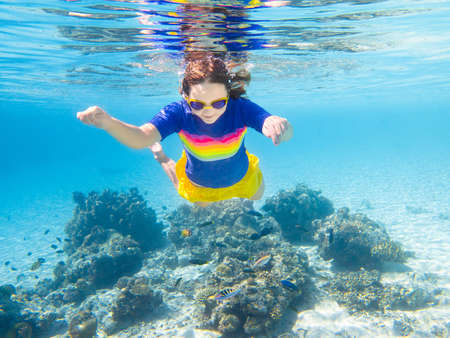 Child snorkeling. Kids swim underwater. Beach and sea summer vacation with children. Little girl watching coral reef fish. Marine life on exotic island. Kid swimming and diving with snorkel and mask. 写真素材