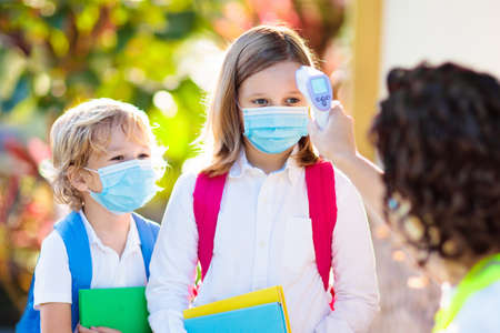 Temperature screening and medical check at school. Child in face mask in class in covid-19 outbreak. Teacher with thermometer at preschool entrance. Social distancing. Coronavirus prevention.
