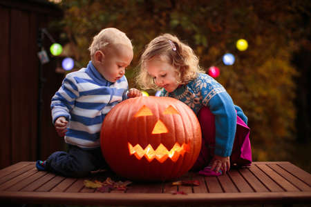 Child carving Halloween pumpkin. Kids carve pumpkins for trick or treat jack o lantern. Autumn activity for children. Little girl in scary witch costume and hat. Kid playing in autumn garden.