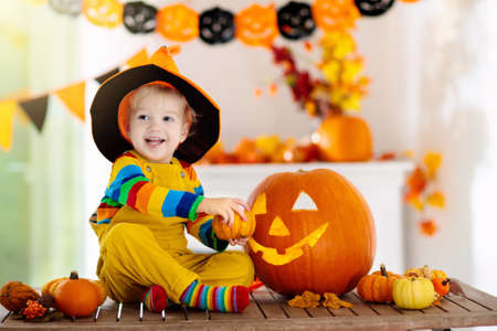 Little boy in witch costume on Halloween trick or treat. Kids carving pumpkin lantern. Children celebrate Halloween at decorated fireplace. Family trick or treating.