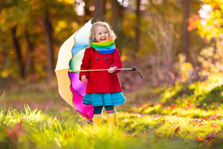 Kid playing out in the rain. Children with umbrella and rain boots play outdoors in heavy autumn rain. Little girl jumping in muddy puddle. Kids fun by rainy fall weather. Child running in storm. Stock Photo