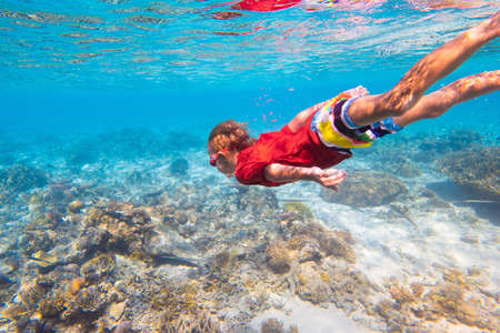 Child snorkeling. Kids swim underwater. Beach and sea summer vacation with children. Little girl watching coral reef fish. Marine life on exotic island. Kid swimming and diving with snorkel and mask. Standard-Bild