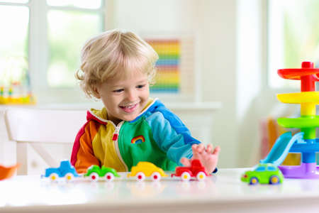 Little boy playing toy cars. Young kid with colorful educational vehicle and transport toys. Child driving car to rainbow parking garage. Kids at home or daycare. Kindergarten or preschool game.