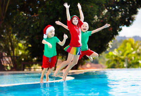 Christmas vacation on tropical island. Kids in Santa hat playing in swimming pool on family Xmas vacation. Winter holidays at the beach. Travel with children. Boy and girl swim. Merry Christmas card.