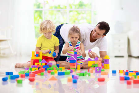 Father and kids play with colorful blocks. Dad, little boy and girl build tower at home or day care. Educational toy for young child. Construction creative game for baby or toddler kid. Stockfoto