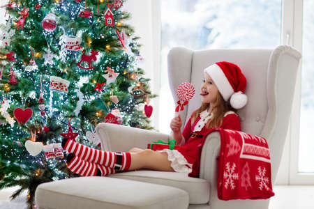 Child with candy decorating Christmas tree and opening present and gift at home. Kid with Xmas gifts and toys. Little girl in Santa dress and hat at fireplace. Family with kids celebrate winter holidays. Foto de archivo