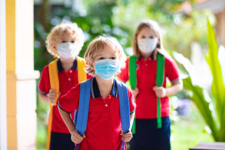 School child wearing face mask during corona virus and flu outbreak. Boy and girl going back to school after covid-19 quarantine and lockdown. Group of kids in masks for coronavirus prevention. Foto de archivo
