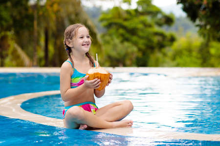 Child with coconut drink in outdoor swimming pool. Kids swim in tropical resort. Healthy exotic fruit refreshment for children. Travel with young kid. Beach and water fun. Summer family vacation. Stockfoto