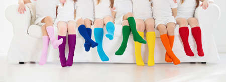 Kids wearing colorful rainbow socks. Children footwear collection. Variety of knitted knee high socks and tights. Child clothing and apparel. Kid fashion. Legs and feet of little boy and girl group. Archivio Fotografico