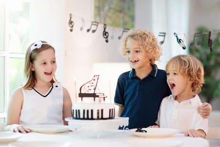 Music and piano theme kids birthday party. Kid with black and white cake. Child blowing candles and opening present. Little boy celebrating birthday. Event for young pianist. Festive decoration.