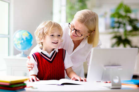 Online remote learning. School kids with computer having video conference chat with teacher and class group. Mother helping son. Child studying from home. Homeschooling in coronavirus outbreak. Zdjęcie Seryjne