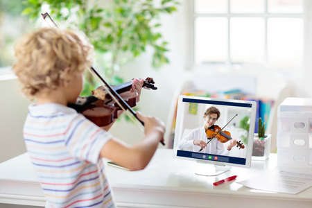Child playing violin. Remote learning from home. Arts for kids. Little boy with musical instrument. Video chat conference lesson. Online music tuition. Creative children play song. Classical education Reklamní fotografie