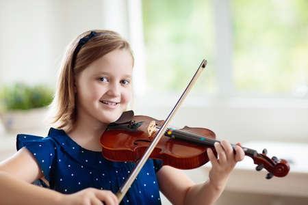 Child playing violin. Remote learning from home. Arts for kid. Little girl with musical instrument. Video chat conference lesson. Online music tuition. Creative children play song. Classical education