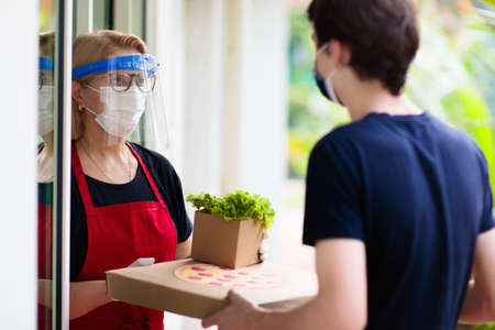 Food delivery in lockdown. Take away food during coronavirus outbreak. Restaurant owner in face mask holding pizza and salad box. Stay home and be safe. Meal order in covid-19 pandemic.