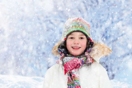 Child playing with snow in winter. Little boy in colorful jacket and knitted hat catching snowflakes in winter park on Christmas. Kids play and jump in snowy forest. Snow ball fight for children.