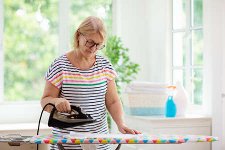 Senior woman ironing clothes. Female folding clothes at iron board. Home chores. Housewife cleaning house. Reklamní fotografie