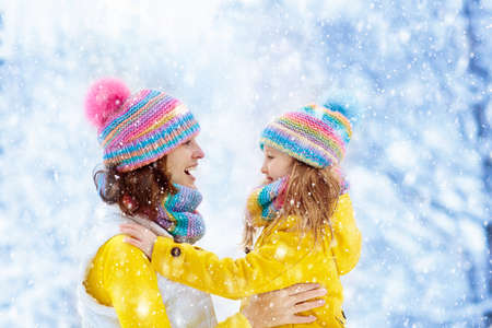 Mother and child in knitted winter hats play in snow on family Christmas vacation. Handmade wool hat and scarf for mom and kid. Knitting for kids. Knit outerwear. Woman and little girl in snowy park. Standard-Bild