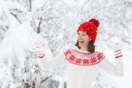 Young woman in knitted sweater playing snow ball fight in winter. Girl in family snow balls game. Female in knit handmade hat and mittens with Christmas snowflake design having fun in snowy park.