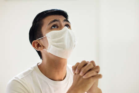 Pray for coronavirus victim. Asian man in face mask praying for sick. Patient in hospital chapel or church during Covid-19 outbreak. Virus pandemic. People worship. Doctor saying a prayer.