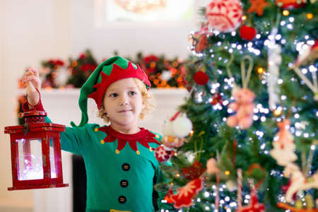 Child decorating Christmas tree at home. Little boy in elf costume and hat with Xmas ornament. Family with kids celebrate winter holidays. Kids decorate living room and fireplace for Christmas.