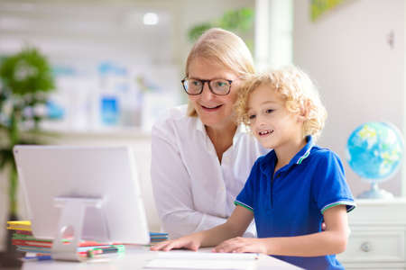 Online remote learning. School kids with computer having video conference chat with teacher and class group. Mother helping son. Child studying from home. Homeschooling in coronavirus outbreak. Stock Photo