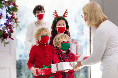 Family with child at grandmother on Christmas day in covid-19 outbreak. Kids in face mask with gifts at home front door. Safe Xmas celebration with grandparents during coronavirus quarantine. Stock Photo