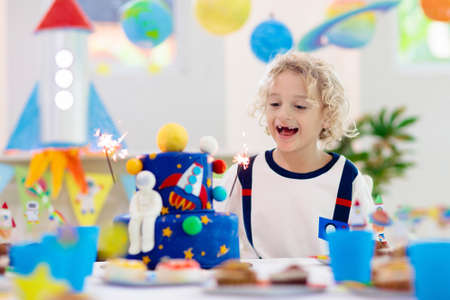 Kids space theme birthday party with cake and cupcakes. Rocket, solar system planet and spaceship decoration for child event. Little boy in astronaut costume blowing candles and opening presents. Stock Photo